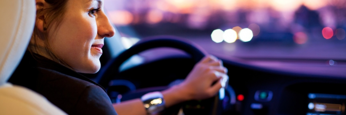 Driving a car at night – pretty, young woman driving her modern